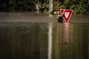 A man holds onto a yield sign after trying to swim out to help a stranded truck driver at NC 301 Highway and Tom Starling Road in Hope Mills on Sunday, Oct. 9, 2016. Both people were rescued.